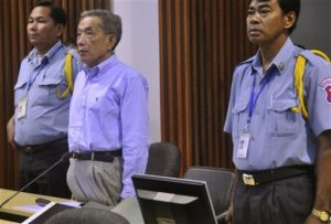 In this photo released by the Extraordinary Chambers in the Courts of Cambodia, Kaing Guek Eav, center, the former chief of the Khmer Rouge's notorious S-21 prison, now known as Tuol Sleng genocide museum, stands in the court room of the U.N.-backed tribunal in Phnom Penh, Cambodia, Wednesday, Nov. 25, 2009. Prosecutors in the genocide trial of the former Khmer Rouge prison chief demanded he be sentenced to 40 years in jail for his role in the killing of thousands of Cambodian prisoners. (AP Photo/Extraordinary Chambers in the Courts of Cambodia) ** EDITORIAL USE ONLY **